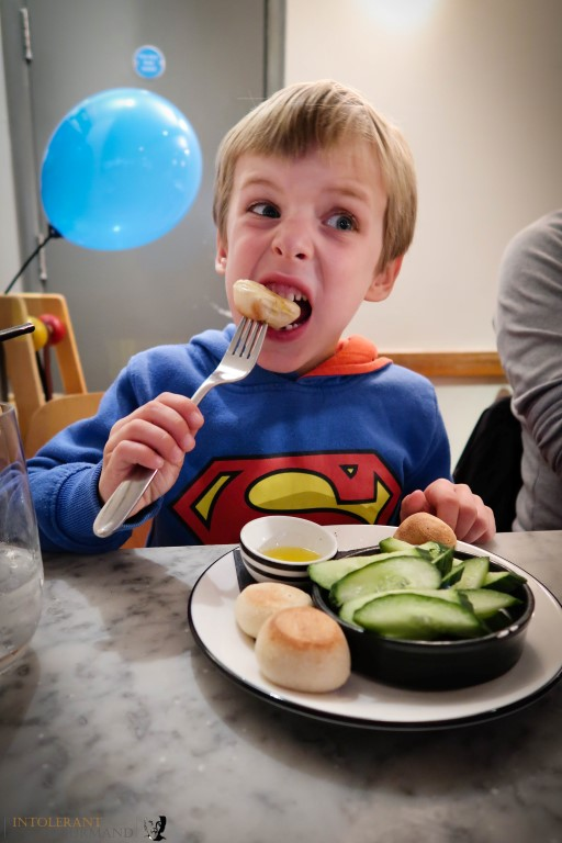 Callum celebrating his birthday at Pizza Express, with free from dough balls and cucumber sticks (gluten free, dairy free) and a blue balloon in the background